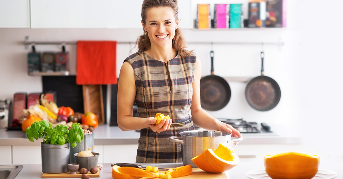 Woman with sliced pumpkin on a kitchen counter